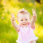 A joyful young white girl in pale pink dress, extends both arms upwards, offering the peace hand gesture. The background is a blurred field of wild yellow flowers.