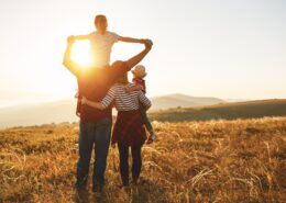 A family stand together on an open landscape, facing away from the camera. The mother holds a young child in one arm while her other arm is wrapped around her husband's waist. The father holds the other child aloft on his shoulders, their hands clasped and outstretched. The sky and landscape ahead is indiscernible due to the intensity of light. The brightest beam is seen through the window formed by the father and child and their clasped hands.
