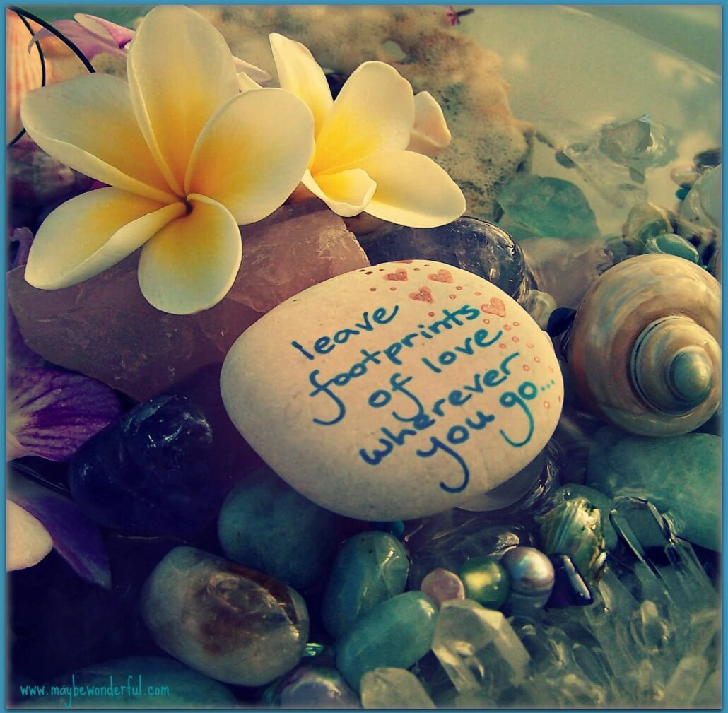 """A large cream stone is surrounded by yellow flowers, seashells and smaller stones of amethyst, lapis lazuli, turquoise, aquamarine, and silver, some sparkling in the light. Hand-written text on the large cream stone reads: """"Leave footprints of love wherever you go."""""""