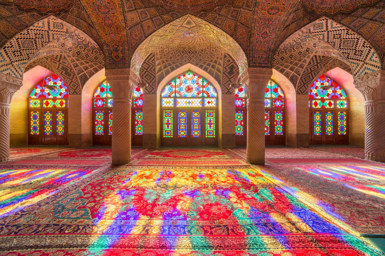 Part of a large sanctuary, spanning four tall columns. Five large windows are recessed within arches beautifully carved and decorated with colourful tile mosaics. The arched windows are fully decorated with panels of stained glass in geometric patterns, and the upper portion of the central window is less saturated than the four windows to the left and right. Sunlight streams in, splashing a bright rainbow of colour across the empty floor and intricately woven carpet. The overall effect is a dazzling kaleidoscope of light.