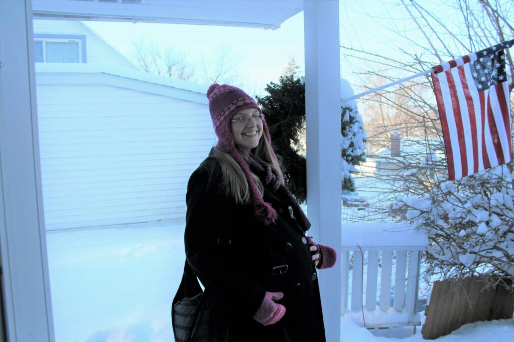 Ruth standing on a porch while pregnant, a snowy landscape behind her.