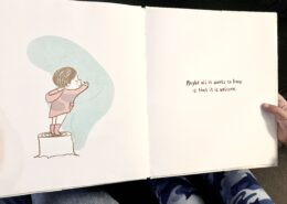 """The book When sadness is at your door by Eva Eland sits on a child's lap as they hold it. The book is opened to a page showing an illustration of a child standing on a tree stump hugging a blue shadow that is their sadness. The text on the page reads """"Maybe all it wants to know is that it is welcome""""."""